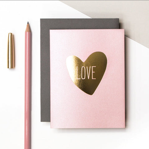 Baby pink greeting card with a gold foil heart on the front inscribed with the word LOVE on the front.  Tell someone you love them any time of the year.