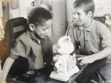 Two kids playing with assistive technology toys