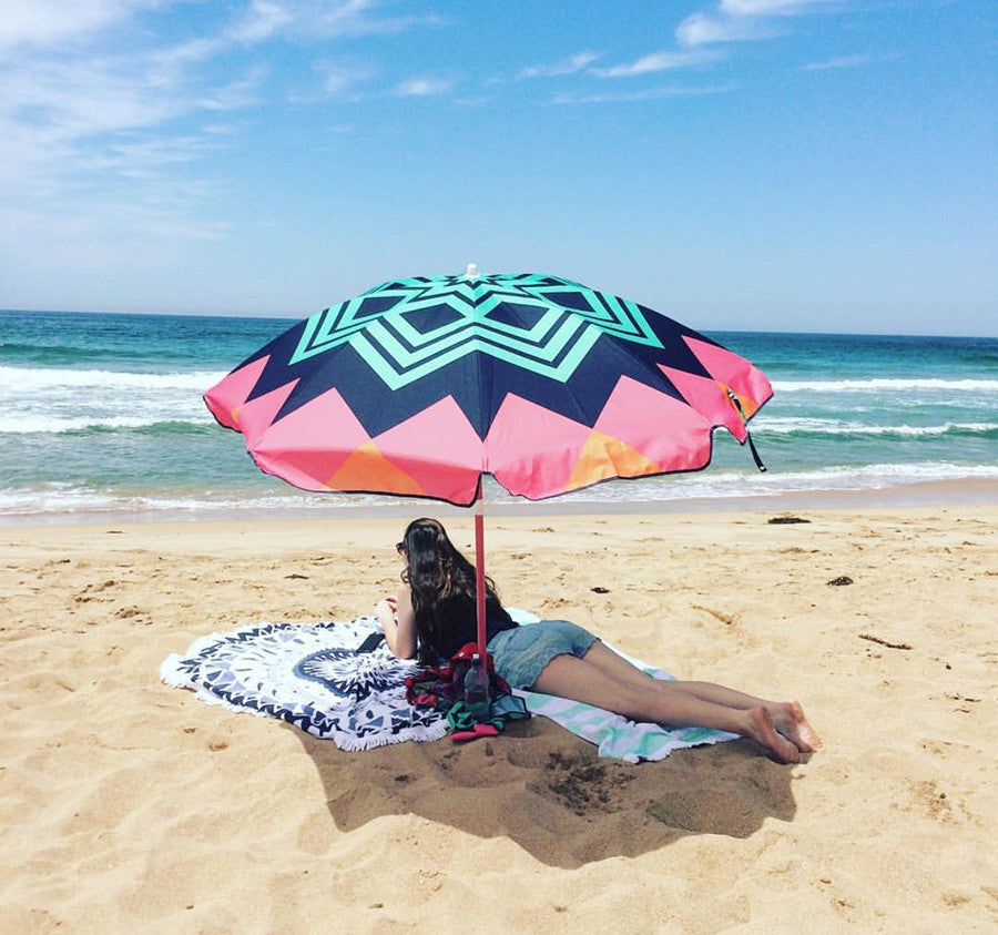 At the beach with a Sunnylife umbrella