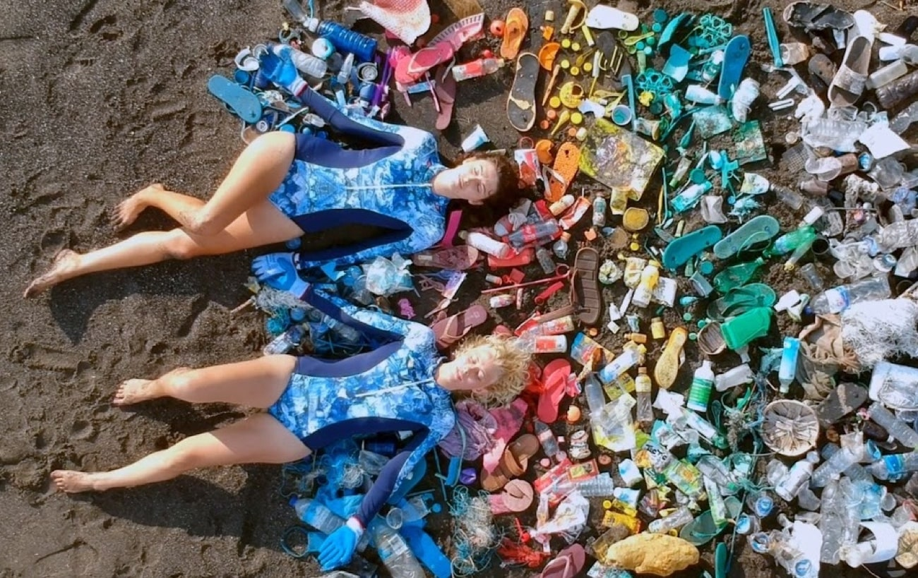 ladies laying on trash collected from the ocean used to make oceanmimic swimwear