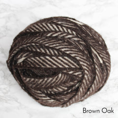 A diagonal striped ball of brown and white blanket yarn for making rag rugs