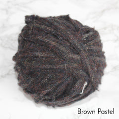 A warm brown coloured ball of blanket material in strips for rag rugging