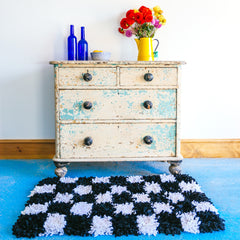 Black and white shaggy checked handmade rag rug inside on a blue floor in front of a chest of drawers display