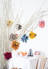 Festive handmade colourful shaggy rag rug Christmas hanging bauble decoration inside on a white tree
