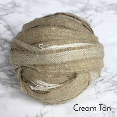 Tan coloured ball of 100% wool blanket yarn on a table.