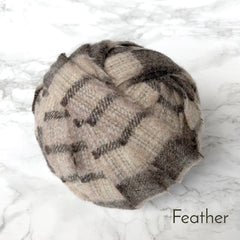 A light brown striped ball of blanket yarn in a ball made of 100% wool
