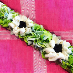Rag rug handmade loopy and shaggy green and white flower trim against a pink fabric background