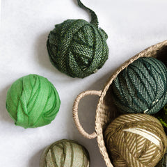 A selection of green Wool Blanket Selvedge Edges balled up for rag rug making - Ragged Life Blanket Yarn