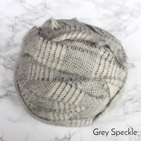 A grey and cream striped ball of 100% wool blanket offcut yarn on a marble floor