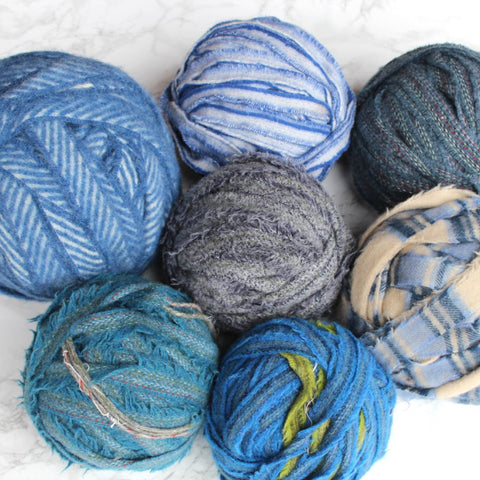 A group of seven balls of 100% wool blanket yarn in different shades of blue