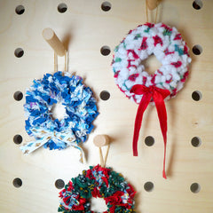 Three small rag rug wreaths hanging on a wooden peg board