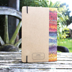 Ragged Life hardback notebook with brown cover and colourful rainbow rag rug image with an elastic hold