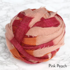 Pink, orange and peach striped blanket yarn made from a plaid blanket in Yorkshire, wrapped into a ball for rag rugging.
