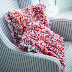 Pink fluffy rag rug cushion made using recycled materials