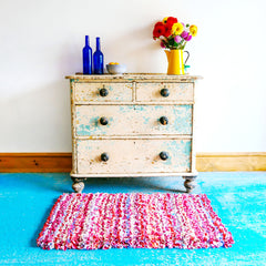 Handmade Pink Striped Shaggy Rag Rug on a blue floor in front of a chest of drawers