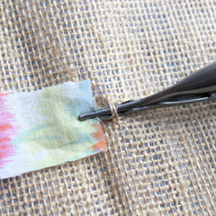Rag Rug Spring Tool gripping onto a fabric strip in the hessian rug