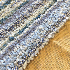 Hessian with blue loopy striped rag rugging partially done