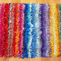 Shaggy rag rug with a colourful rainbow stripe pattern displayed inside on a wooden floor