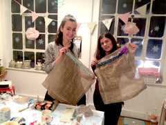 Two women posing with their partially made rag rug cushions at a Ragged Life class
