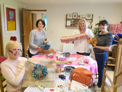 Four women smiling at a rag rug workshop at Ragged Life in Hertfordshire