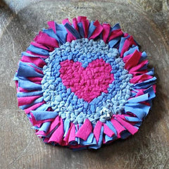 Rag rug handmade flower with a blue background and pink love heart centre with pink and blue petals. Made using the Ragged Life trivet hessian / burlap.