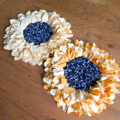 Rag rug handmade flowers with blue centres and white and yellow petals. Made using the Ragged Life trivet hessian / burlap.