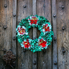 Festive Christmas handmade green and red holly flower rag rug wreath hanging outside on a wooden door