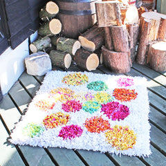 Shaggy rag rug with a colourful polka dot pattern on a white background displayed outside on a wooden barn floor