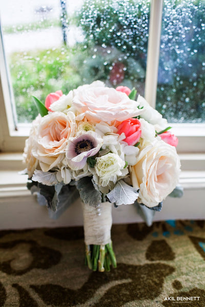 her bouquet comprised of white ohara garden roses hydrangea tulips anemonies ranunculas and dusty miller