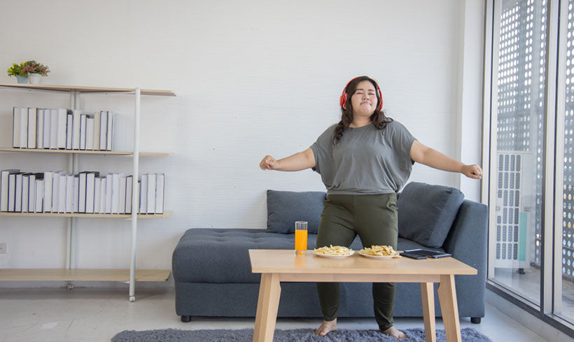 plus size woman dancing with headphones
