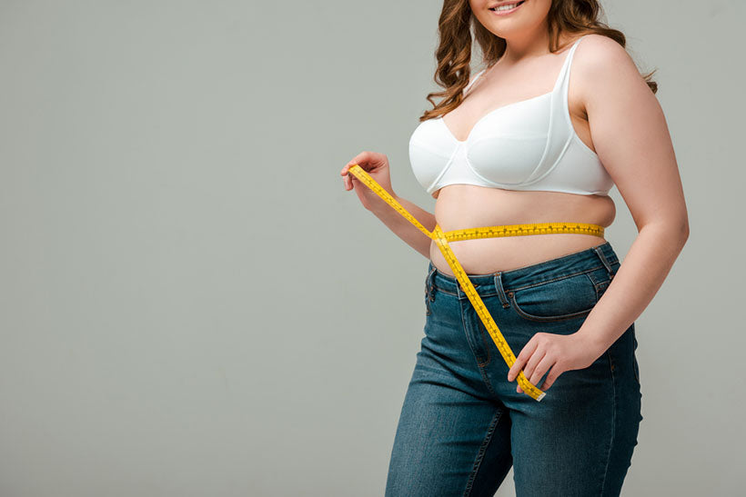 plus size woman measuring waist