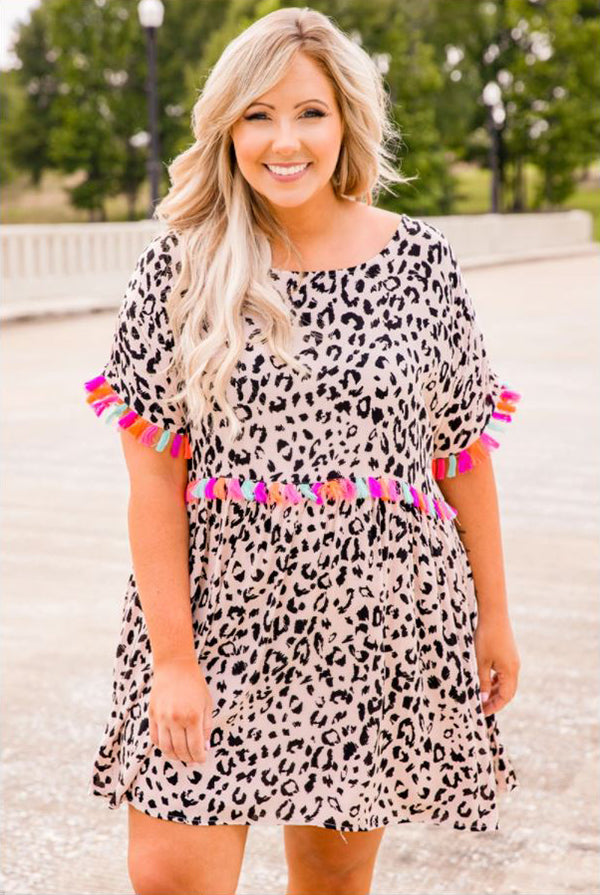a smiling woman wearing a stepping ahead dress in leopard print