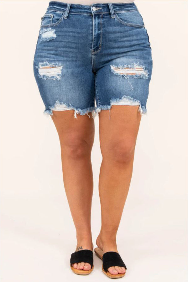 a close up of a full figured woman sporting a pair of wont change my hearts shorts medium wash