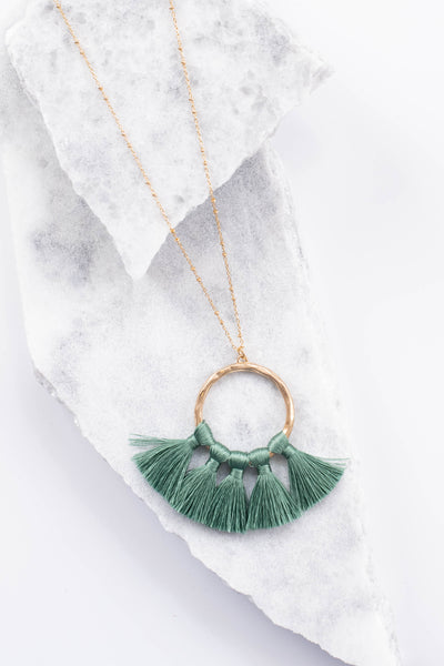 necklace, gold chain, gold ring, green tassels