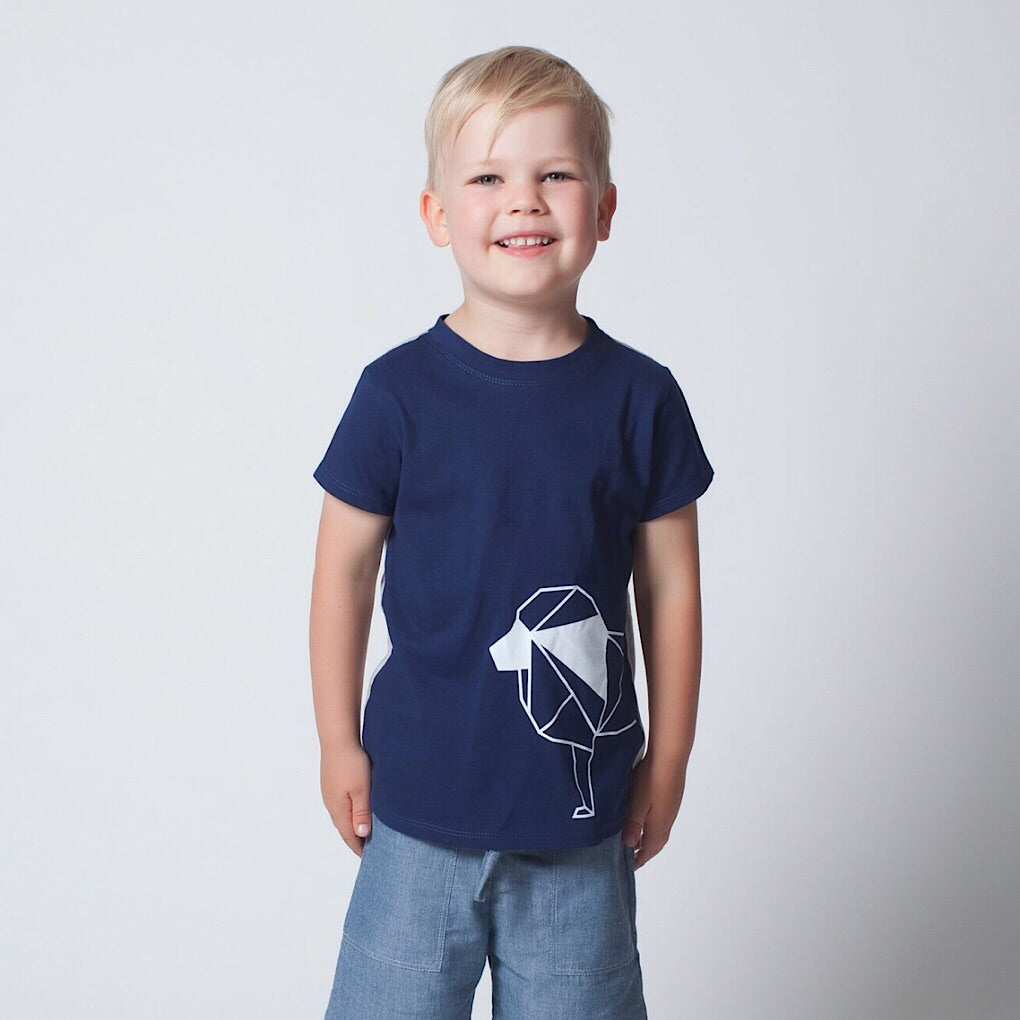 Made from premium 100% certified organic cotton. ReCreates' unisex short sleeve kids top is deep blue in the front with a charming geometric outline of a lion.