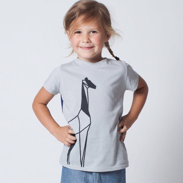 Made from premium 100% certified organic cotton. ReCreate unisex short sleeve kids top is blue/grey in the front with a charming geometric outline of a giraffe. Wholesome Gifts Australia.