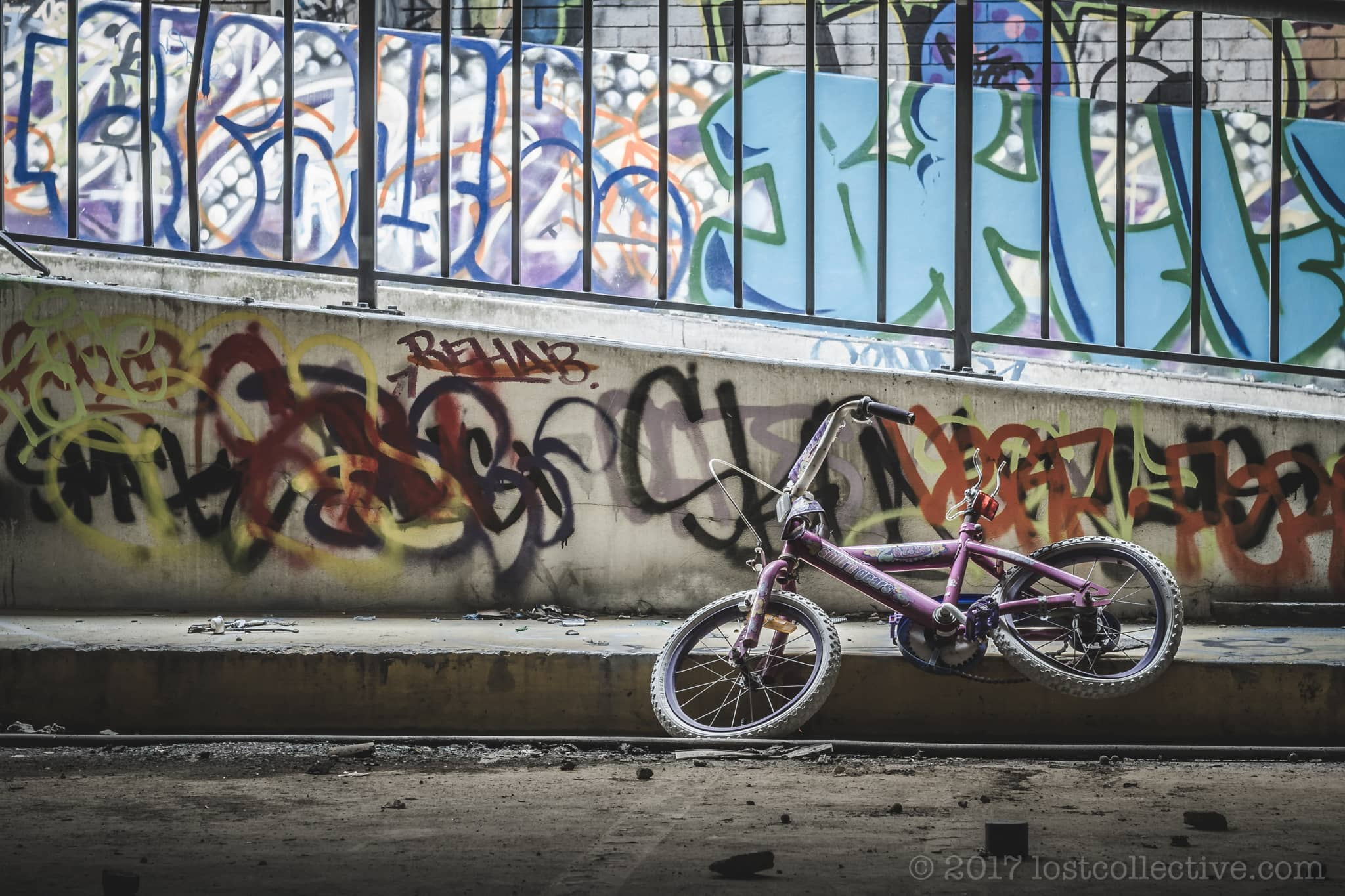 a young girls bicycle against a backdrop of graffiti in the abandoned balmain leagues club - lost collective