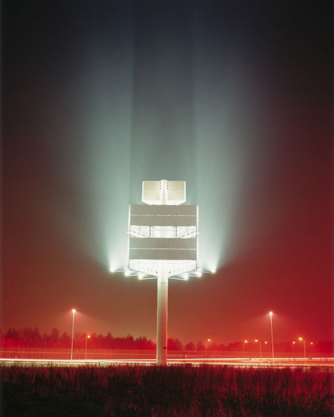 a large tower light at night with a red hue fog - dan holdsworth