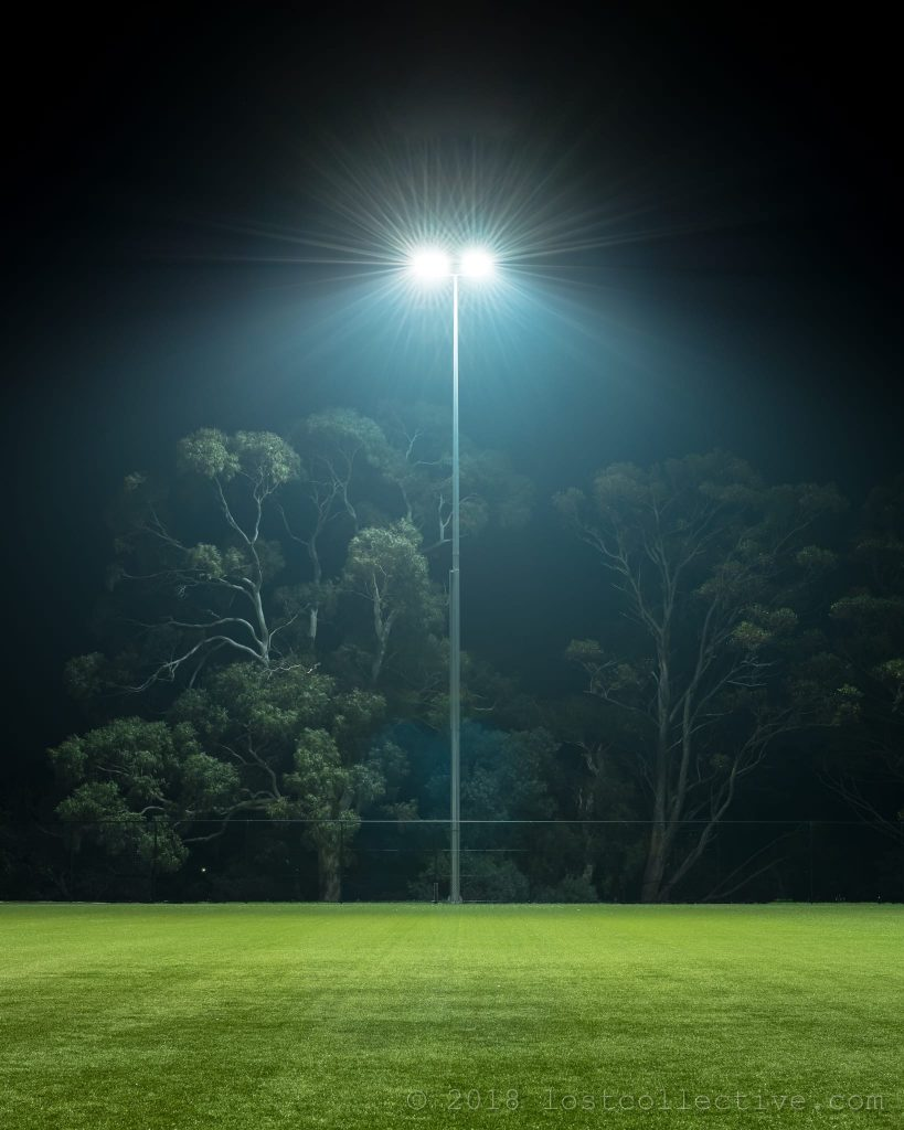 a field light at night above green synthetic grass - lost collective