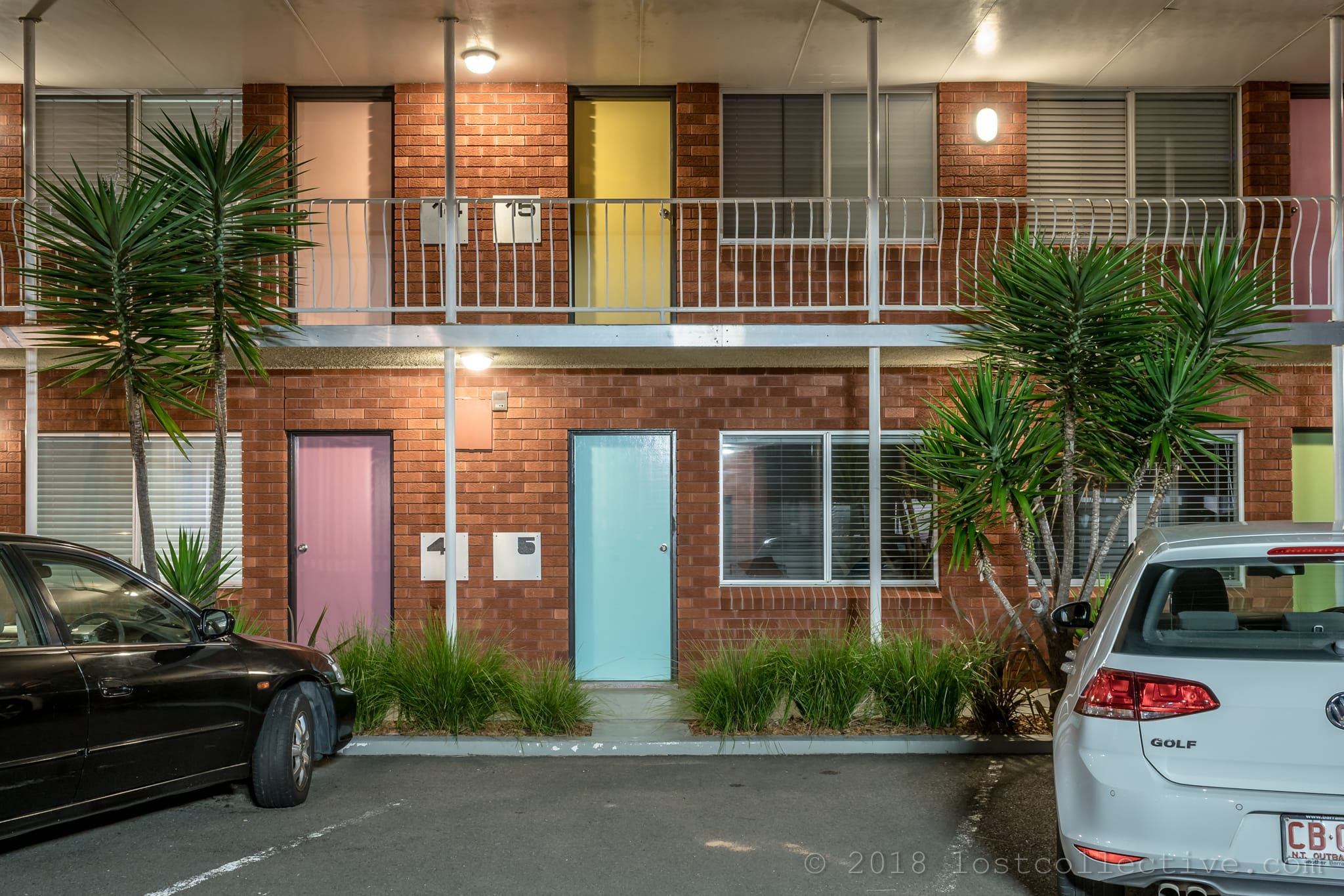 a red brick motel with pastel coloured doors and a tree - lost collective