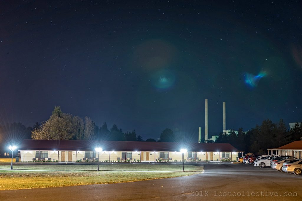 a motel at night with a power station rising behind - lost collective