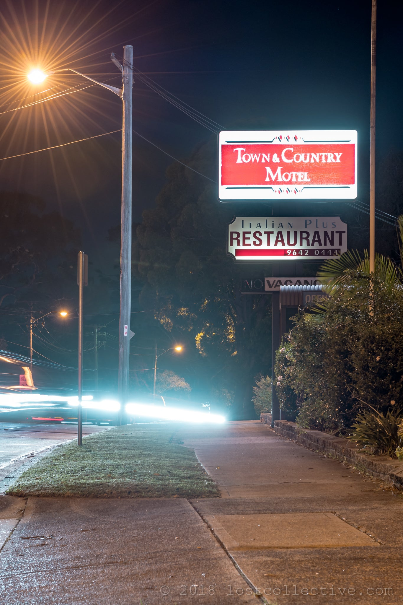 the town and country motel sign at night from the roadside