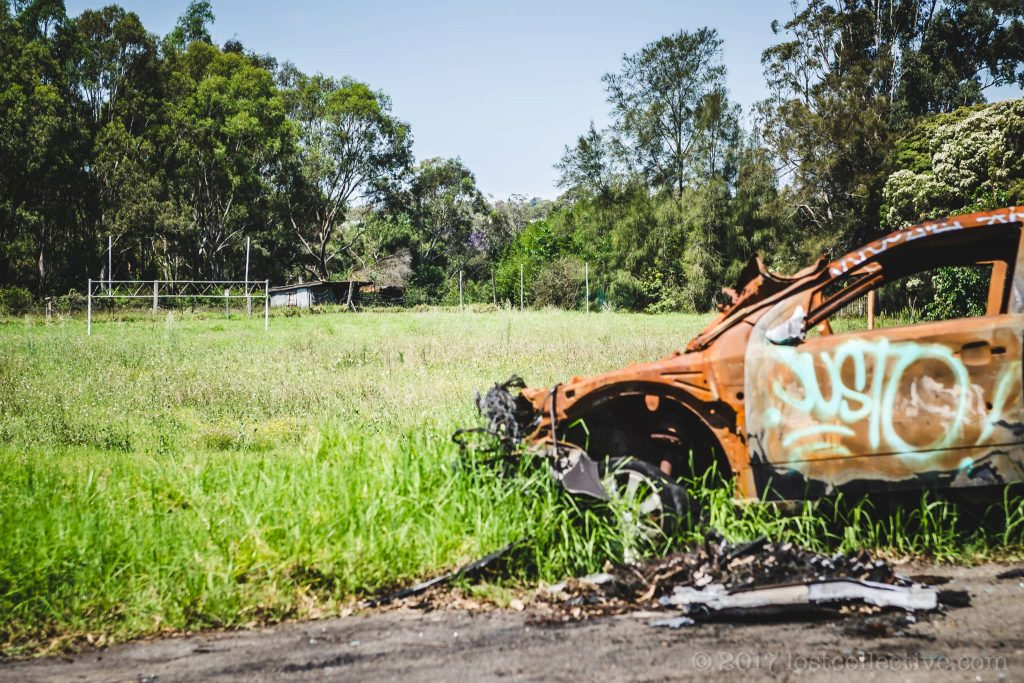 A burnt out car sits on the edge of the now overgrown football field in macquarie boys technology high - lost collective