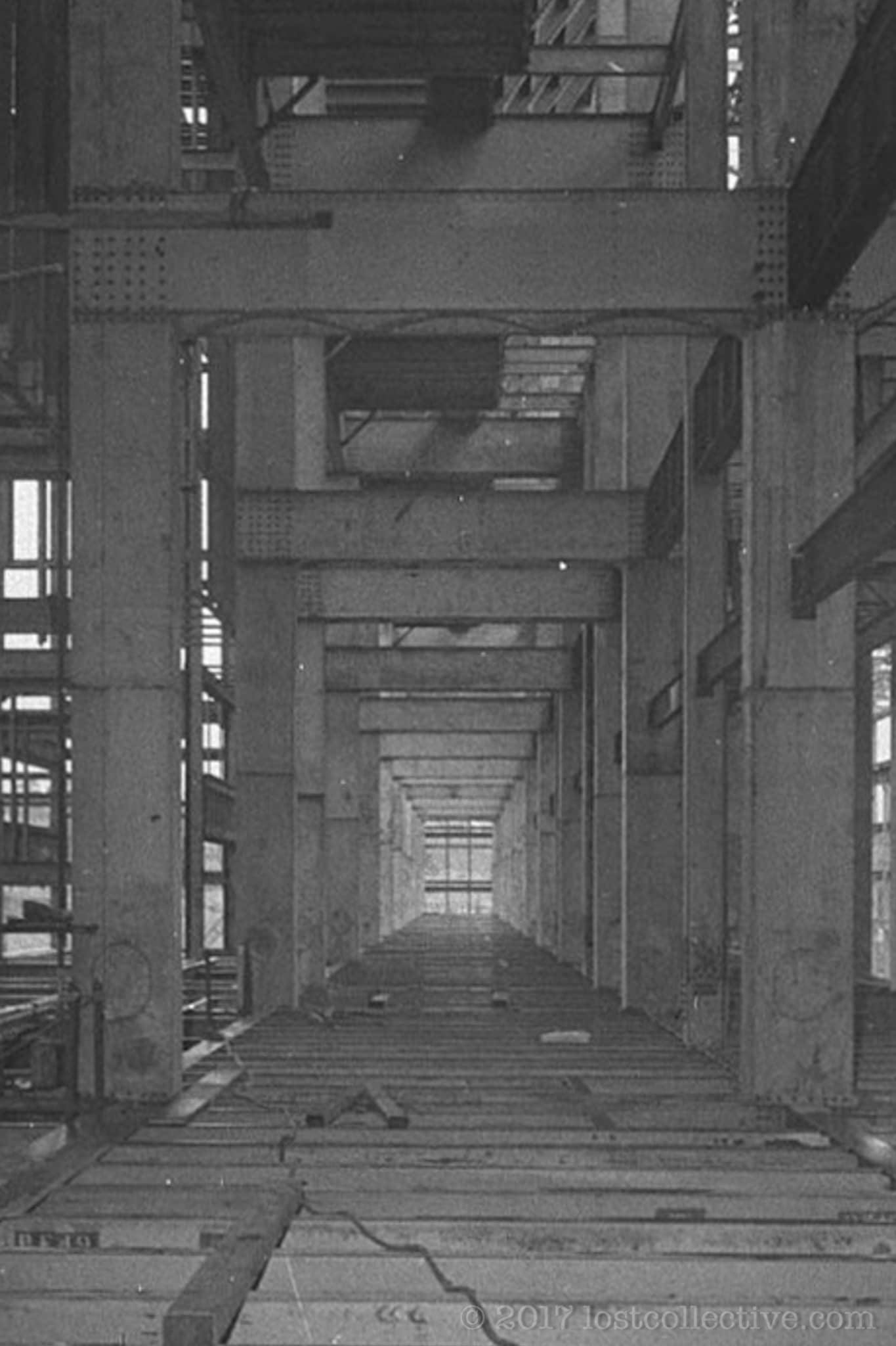 a historical photograph of large pylons supporting an overhead walkway in the abandoned wangi power station - lost collective<img src=
