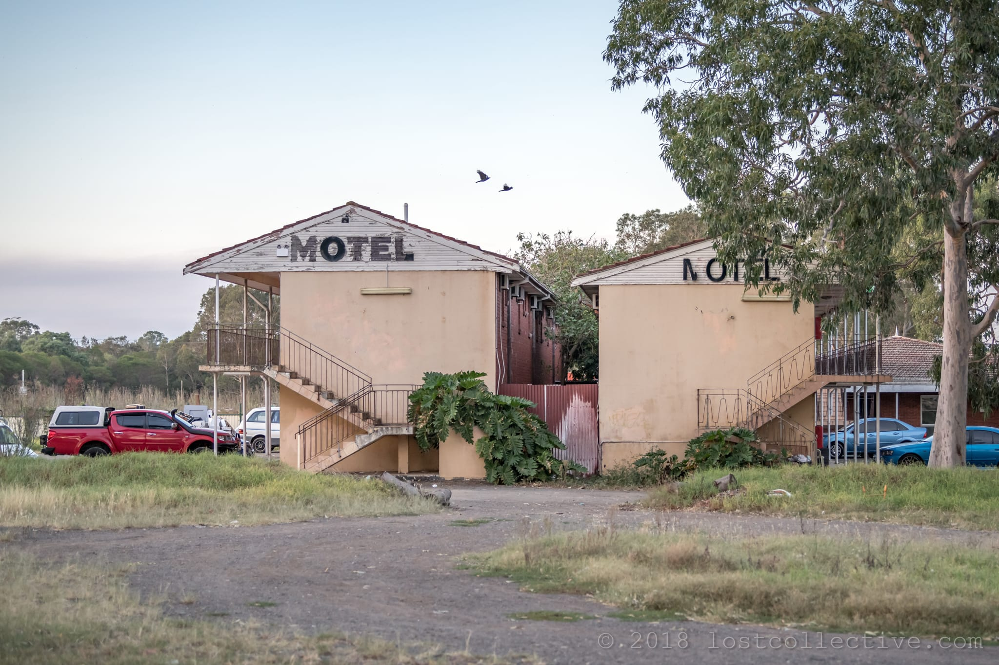 the side of a run down motel during the day with a gravel road, grass and trees - lost collective