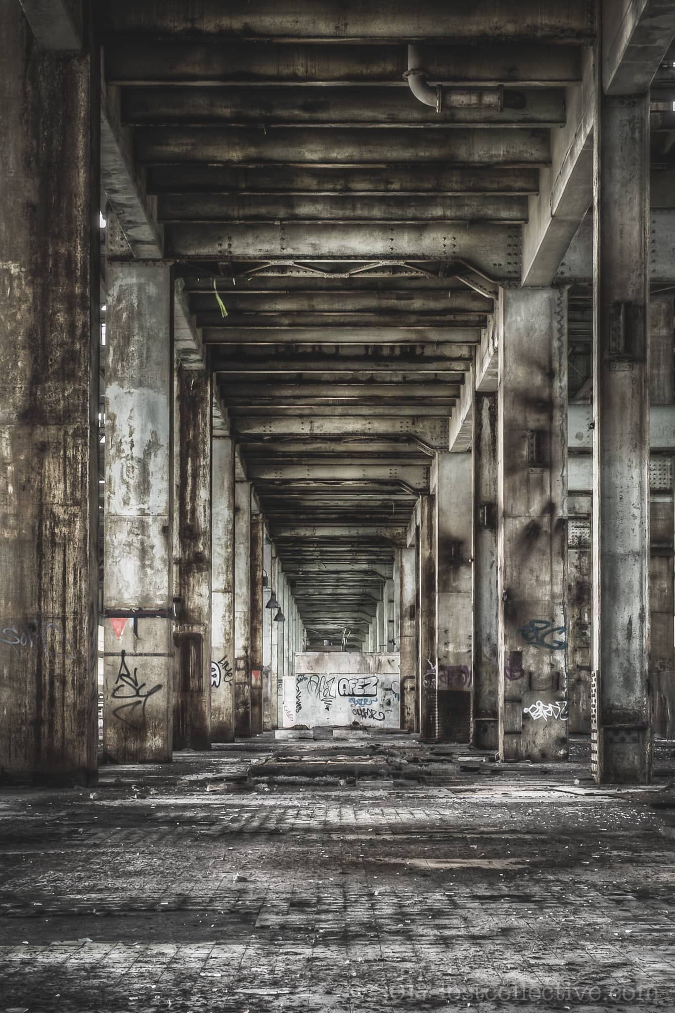 large pylons supporting an overhead walkway in the abandoned wangi power station - lost collective