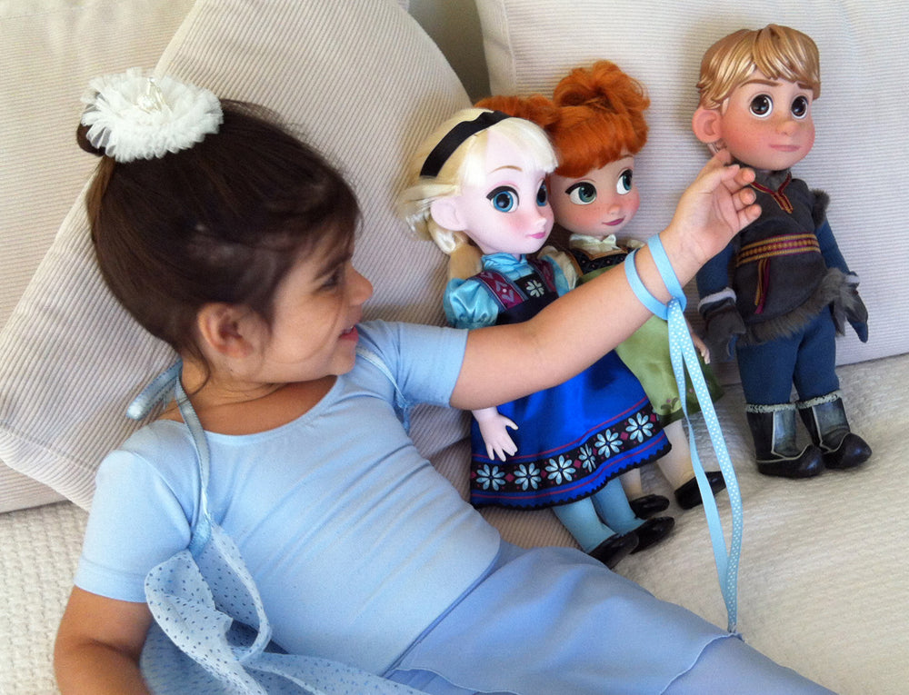 Girl playing with Disney Frozen dolls