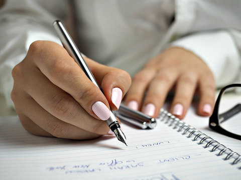 Woman with pink nails writing in a notebook