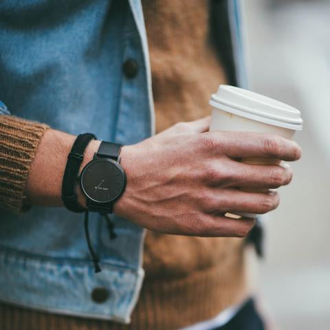 A jacket and arm and coffee cup and the Bells watch by John Taylor