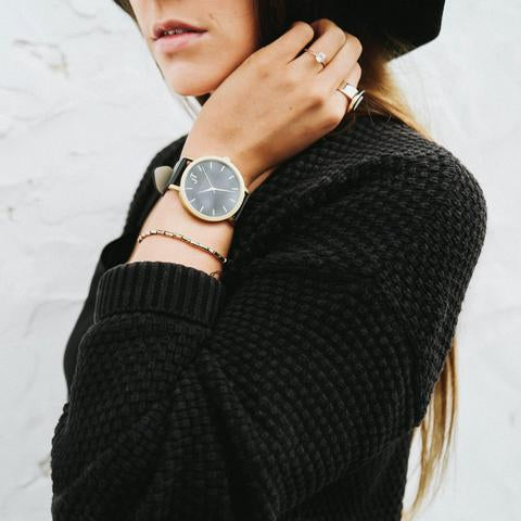 Image of a model with the John Taylor Bondi black and gold watch